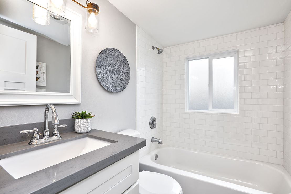 Bathroom interior with white vanity topped with gray countertop